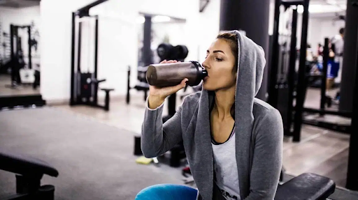 woman with a grey hoodie drinking a post workout shake in a gym