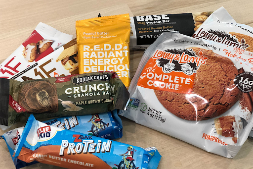 group photo of many different protein bars and protein cookies